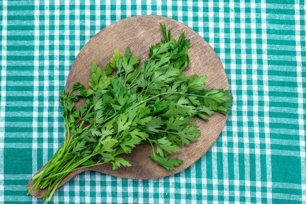 茶色の木製の机の上に隔離された新鮮な緑と明るい青、緑の葉の食べ物の食事の上面図