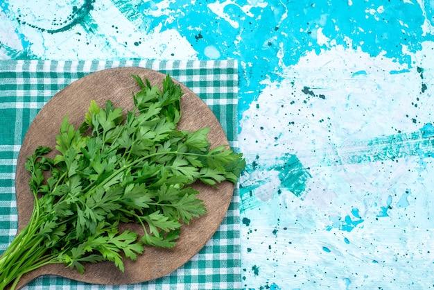 茶色の木製の机の上に隔離された新鮮な緑の上面図、および明るい青、緑の葉製品食品ミール