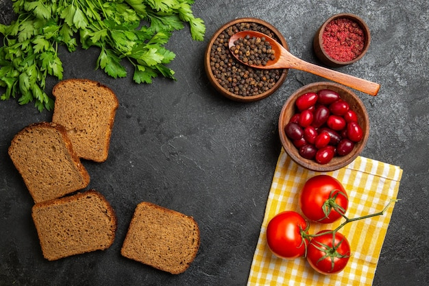 Вид сверху свежей зелени с буханками хлеба кизила и помидорами на серой поверхности