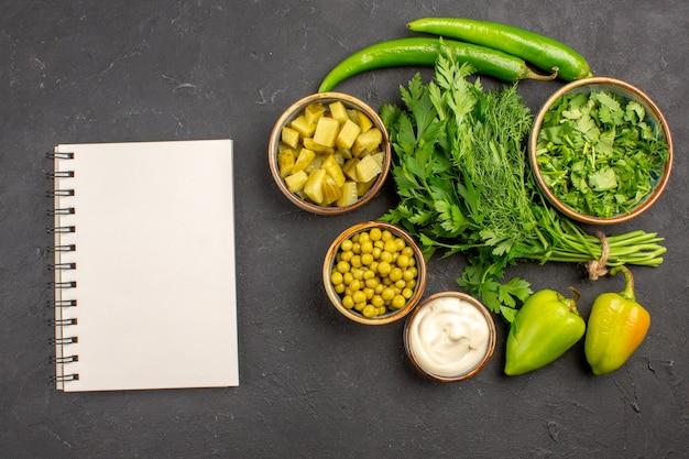 暗い表面にサラダの材料と新鮮な緑の上面図