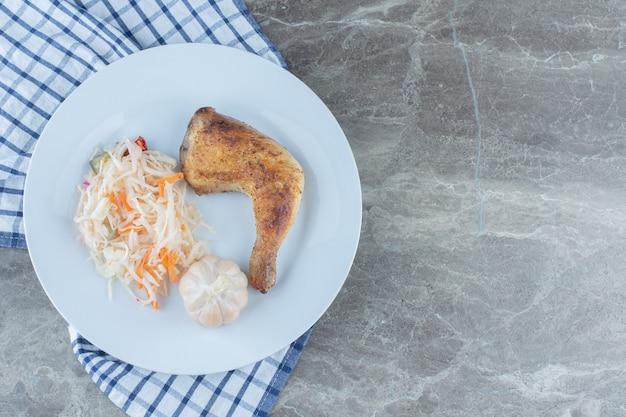 Вид сверху свежей жареной куриной ножки и квашеной капусты на белой тарелке.