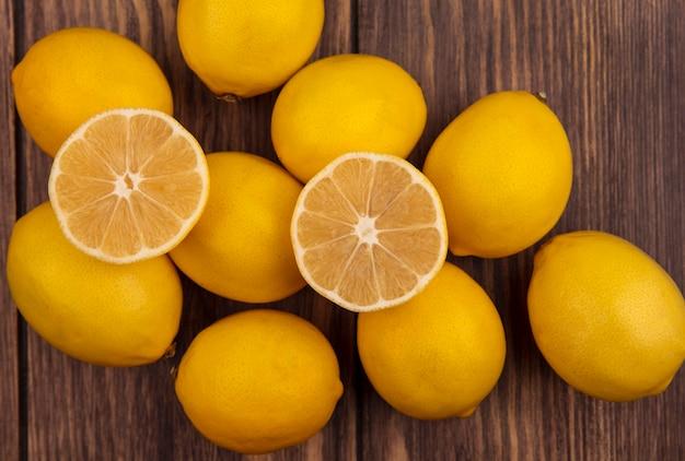 Вид сверху свежих половин и целых лимонов, изолированных на деревянной поверхности