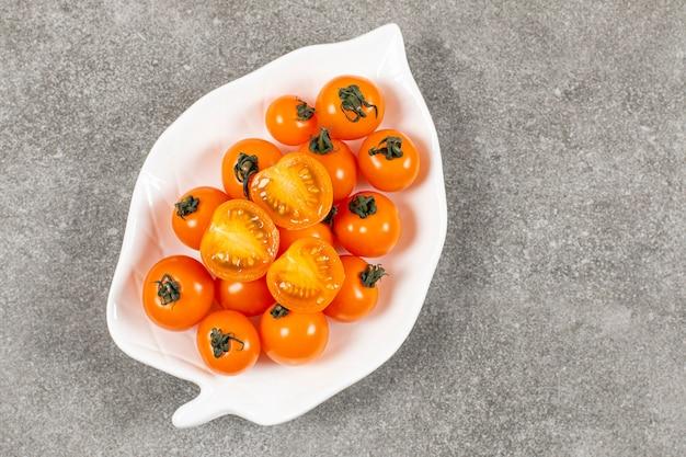 白いプレート上の新鮮なハーフカットとトマト全体の上面図。
