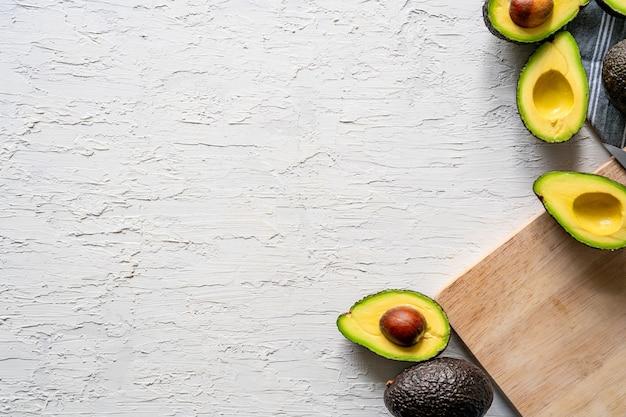 흰색 표면에 있는 신선한 반으로 자른 아보카도와 나무 커팅 보드의 상단 보기, 복사 공간 무료 사진