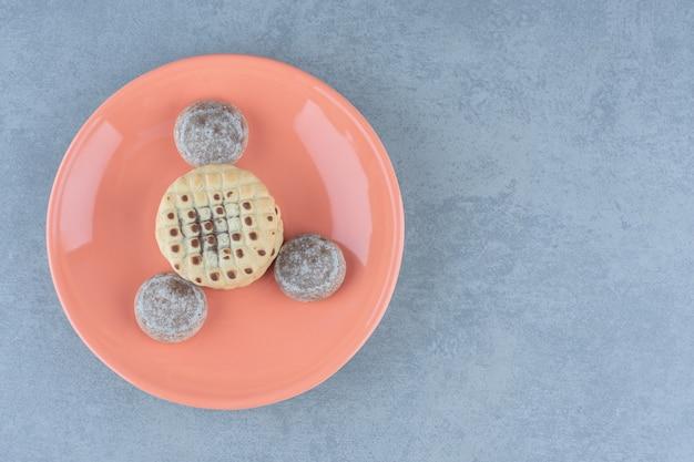 新鮮な自家製クッキーの上面図。オレンジ色のプレートに美味しいおやつ。