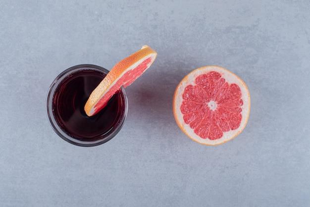 Вид сверху свежего домашнего сока с ломтиками грейпфрута на серой поверхности