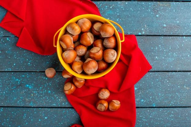 Вид сверху свежих орехов хволе внутри желтой корзины на синей поверхности