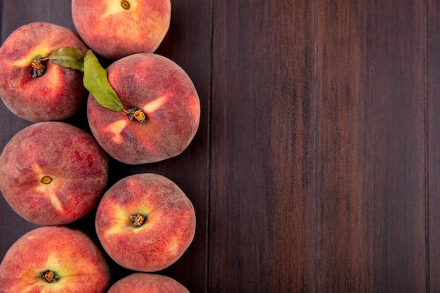 Вид сверху свежих сочных вкусных персиков на дереве с копией пространства