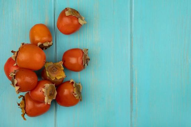 コピースペースと青い木製の壁に分離された新鮮なジューシーな柿の上面図