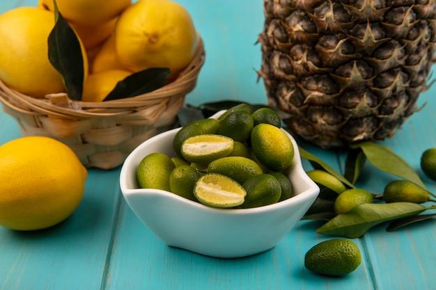 Вид сверху свежих кинканов на миске с лимонами на ведре с ананасом, изолированным на синем деревянном фоне