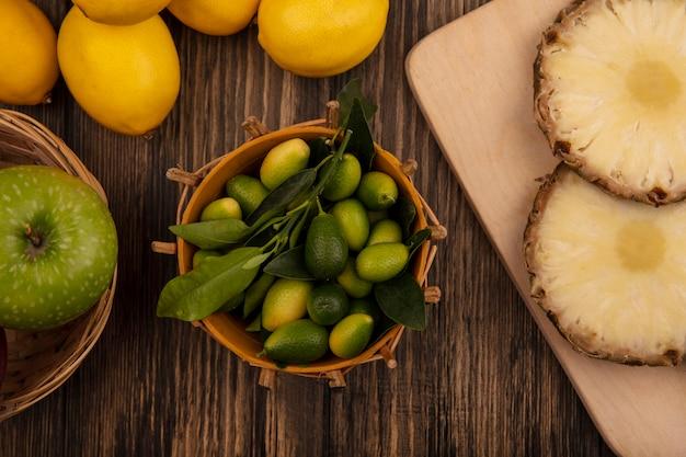 木製のキッチンボード上のパイナップルとバケツの上の新鮮なキンカンの上面図木製の壁に隔離されたレモンとバケツの上のリンゴ