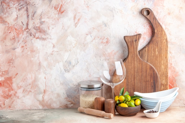 신선한 금귤의 상위 뷰는 다채로운 표면에 냄비 나무 커팅 보드 유리 잔 쌀을 쌓아