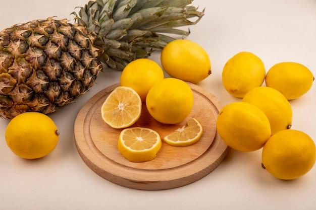 白い壁に分離されたパイナップルとレモンと木製のキッチンボード上の新鮮なレモンスライスの上面図