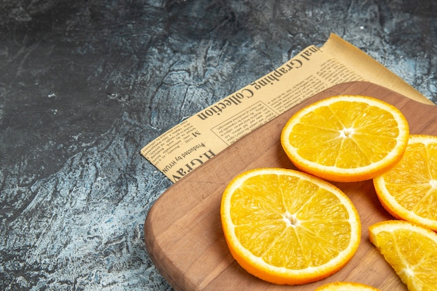 灰色の背景に新聞の木製ボード上の新鮮なレモンスライスの上面図