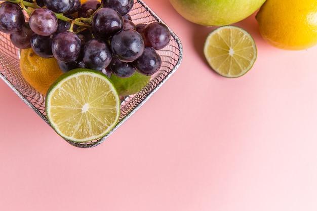 淡いピンクの表面にリンゴとブドウとフライヤー内の新鮮なレモン柑橘類の上面図