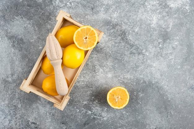 Вид сверху свежих лимонов в деревянном ящике над серой поверхностью.