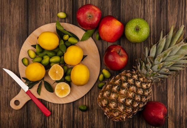 사과와 파인애플 나무 표면에 고립 된 나무 주방 보드에 고립 된 신선한 레몬의 상위 뷰