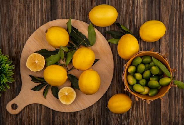 Вид сверху свежих лимонов, изолированных на деревянной кухонной доске с кинканами на ведре на деревянном фоне