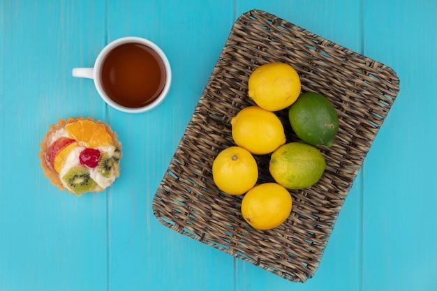 青い木製の背景にお茶とフルーツのタルトとバケツの上の新鮮なレモンの上面図