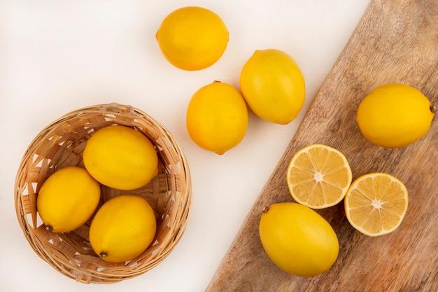 白い背景の上の木製のキッチンボードに分離されたレモンとバケツの上の新鮮なレモンの上面図