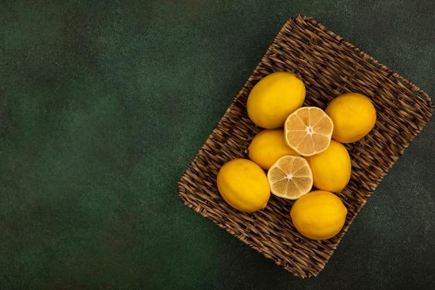 Вид сверху свежих лимонов на плетеном подносе на зеленом фоне с копией пространства
