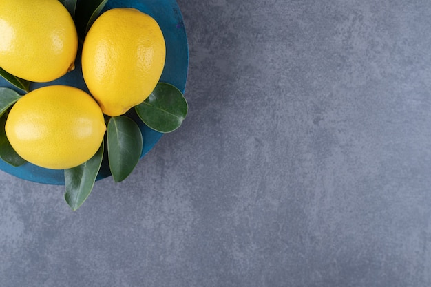 회색 배경 위에 파란색 접시에 신선한 레몬의 상위 뷰.