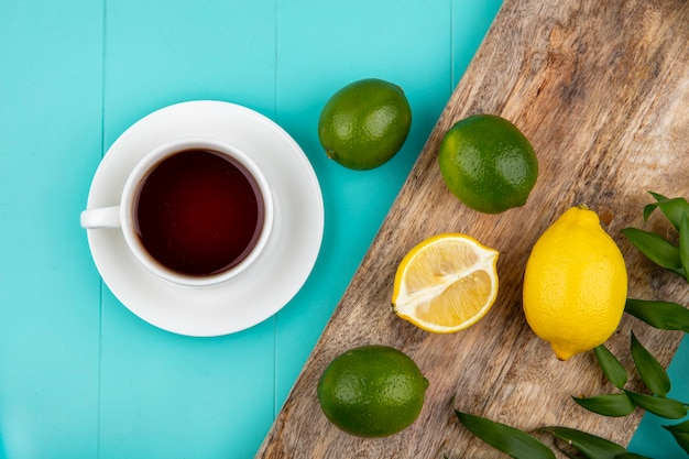青のお茶のカップを持つ木製キッチンボード上の新鮮なレモンのトップビュー