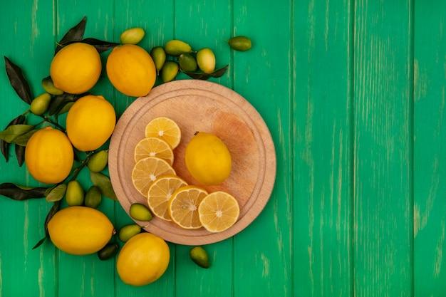 Вид сверху ломтиков свежих лимонов на деревянной кухонной доске с кинканами и лимонами, изолированными на зеленой деревянной стене с копией пространства