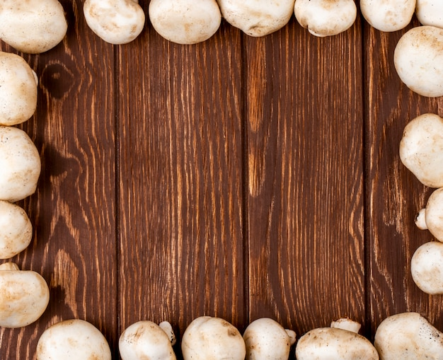 コピースペースを持つ素朴な木製の背景にフレームとして配置された新鮮なキノコシャンピニオンのトップビュー