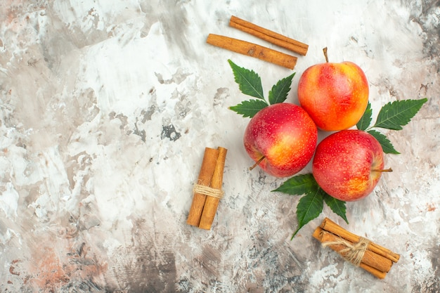 Вид сверху на свежие натуральные красные яблоки и лайм с корицей слева на смешанном цветном фоне