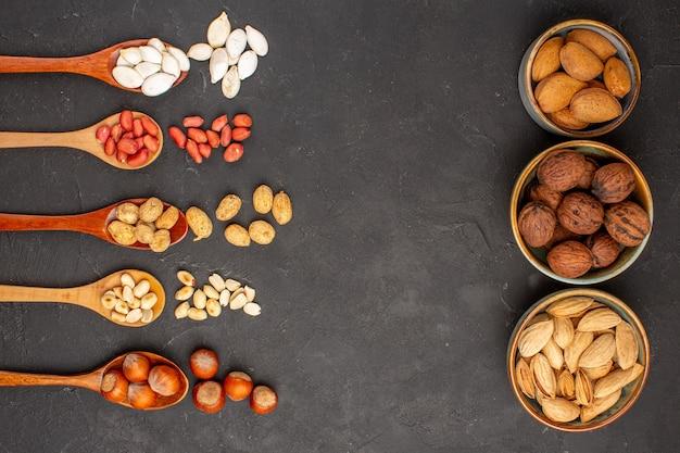 Вид сверху свежих орехов, арахиса и других орехов на темной поверхности
