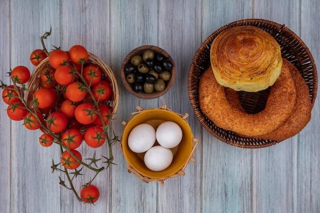 灰色の木製の背景の上のバスケットにパンとバケツにつるトマトと木製のボウルに新鮮なオリーブの上面図