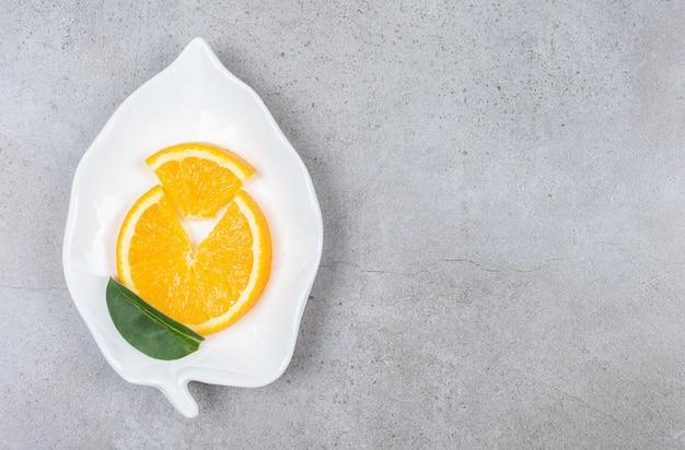 Вид сверху свежей апельсиновой дольки на белой тарелке с листом.
