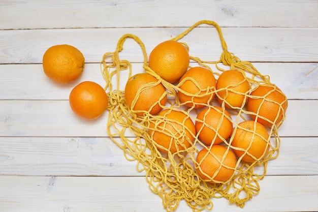 白い素朴な背景の上にストリングバッグの新鮮なオレンジの上面図。