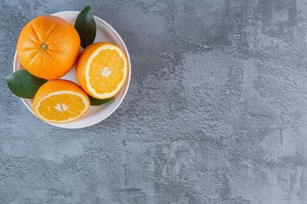 新鮮な有機柑橘系の果物の上面図。プレート上の有機オレンジ。