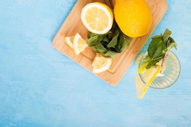 青いヴィンテージの木製の背景にレモンと新鮮な有機デトックス水の上面図