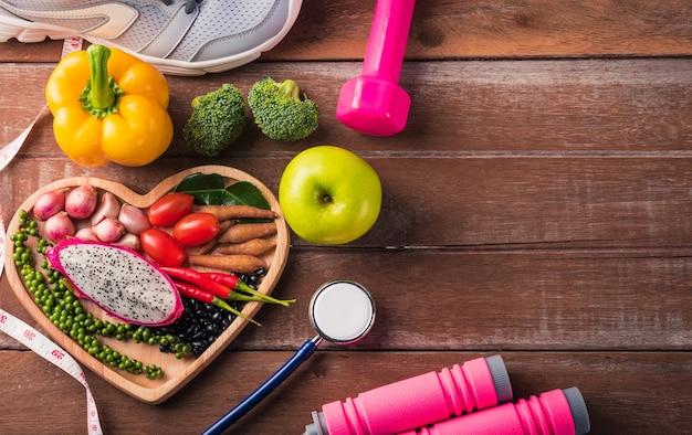 ハートプレートの新鮮な有機果物と野菜の上面図