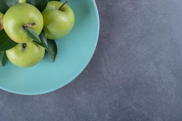 Вид сверху свежих органических зеленых яблок на голубой тарелке.