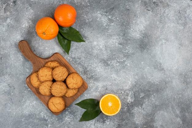 Вид сверху на свежие органические апельсины целые или вырезанные и домашнее печенье.