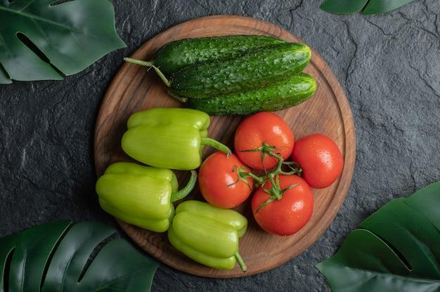 新鮮な有機野菜の上面図。きゅうりのトマトとピーマン。