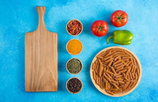 青いテーブルの上に生パスタとスパイスと新鮮な有機野菜の上面図。