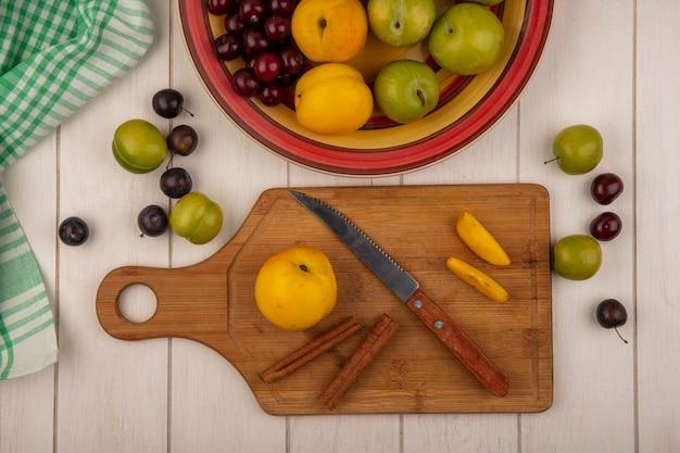 Вид сверху свежего персика на деревянной кухонной доске с ножом с палочками корицы с фруктами, изолированными на белом деревянном фоне
