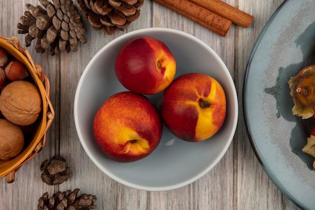 Вид сверху свежих персиков на миске с палочками корицы и сосновыми шишками, изолированными на серой деревянной стене