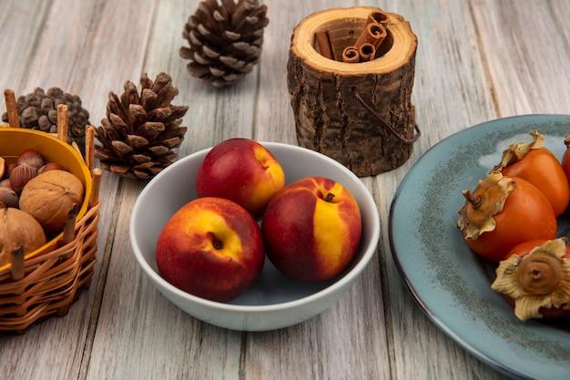 灰色の木製の表面にシナモンスティックとプレート上の柿とボウルの新鮮な桃の上面図