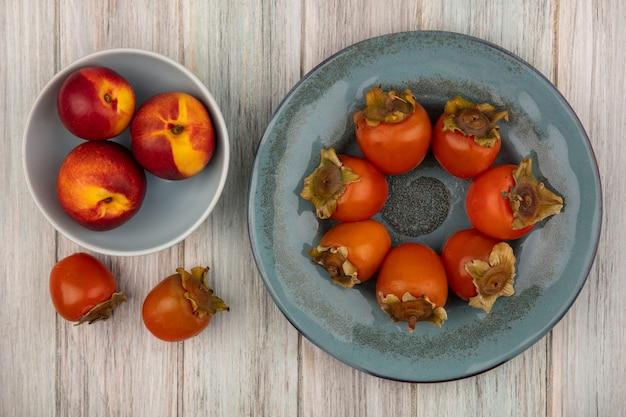 Вид сверху свежих персиков на миске с мягкой хурмой на тарелке на сером деревянном фоне