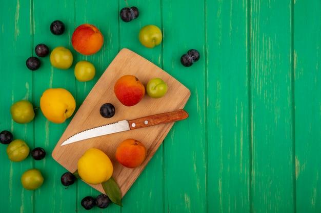 Вид сверху свежих персиков на деревянной кухонной доске с ножом на зеленом фоне с копией пространства