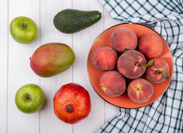 Вид сверху свежих персиков в миске на проверенной скатерти с яблоками, манго, гранатом, изолированным на белом