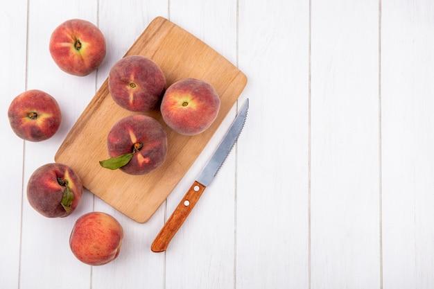 コピースペースを持つ白のナイフで木製キッチンボード上の新鮮な桃のトップビュー