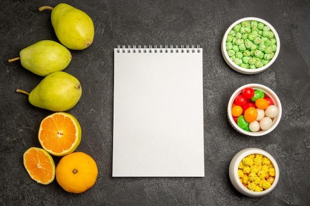濃い灰色のテーブルにみかんとキャンディーと新鮮な梨の上面図