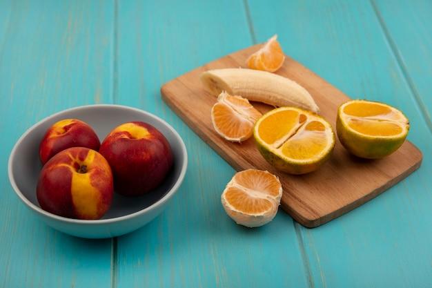 青い木製の壁のバケツに桃とみかんと木製のキッチンボード上の新鮮な皮をむいたバナナの上面図